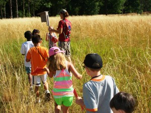 Examining a Bluebird Nest Box in a prarie with a group of children