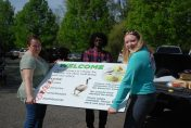 Sanctuary staff holding new welcome sign