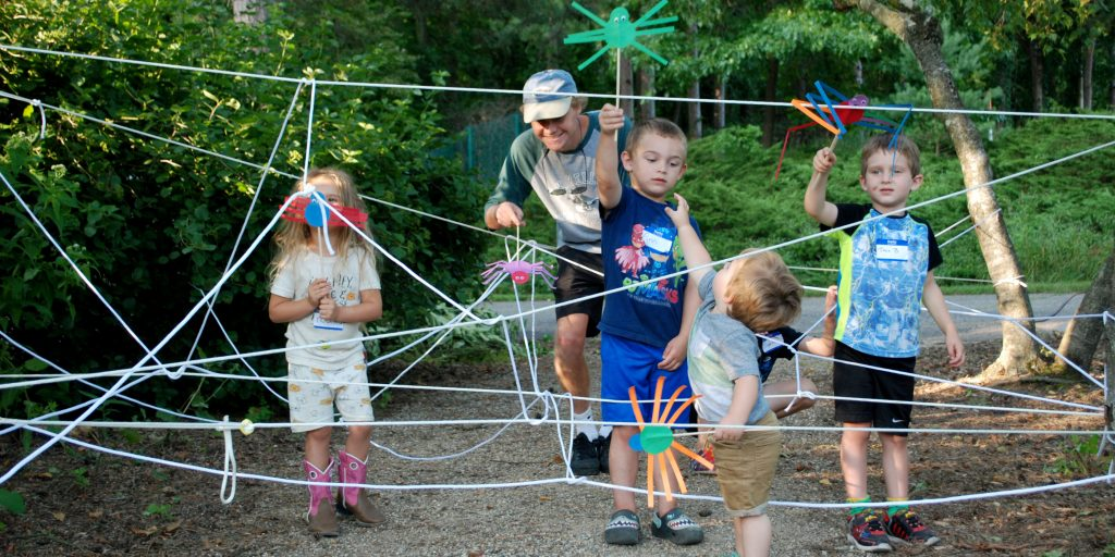 Children play with handmade spider toys at a 2019 Wild Wednesdays event.