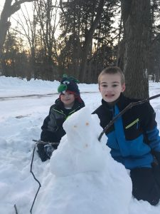 Image of 2 boys in snow suits with a snowman